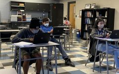 Students in masks sit in physically distanced desks.
