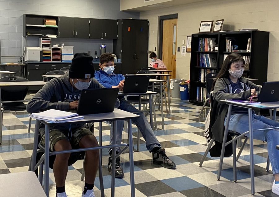 Students+in+masks+sit+in+physically+distanced+desks.