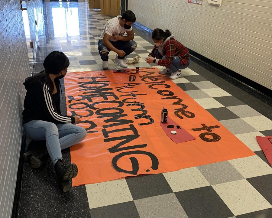 Students decorate a homecoming sign in the hallway.