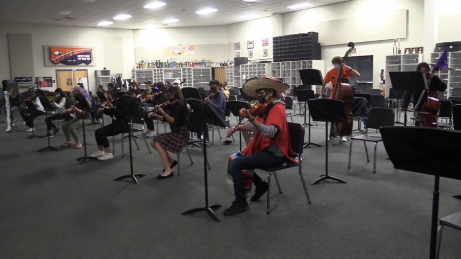 Orchestra students perform while socially distanced.