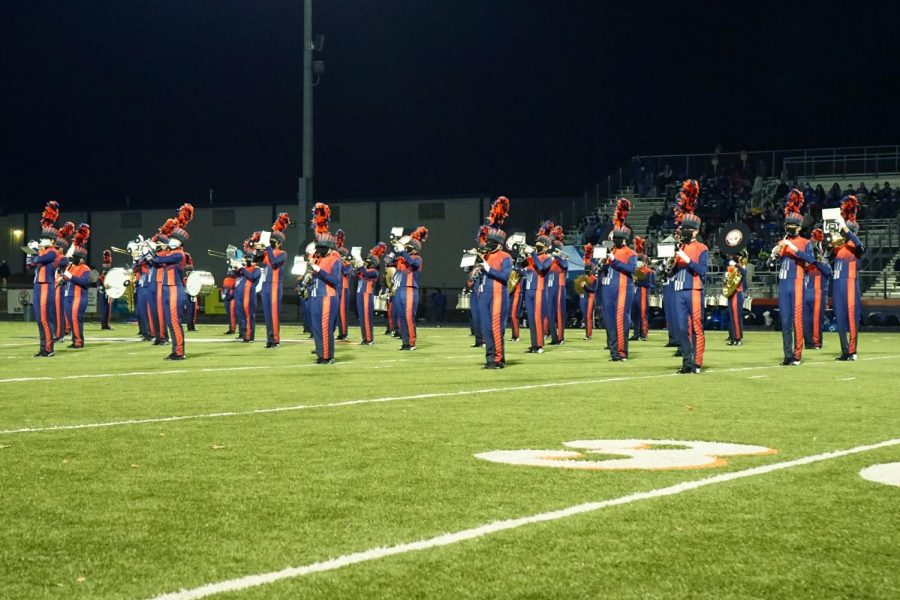 Marching band plays on football field at night