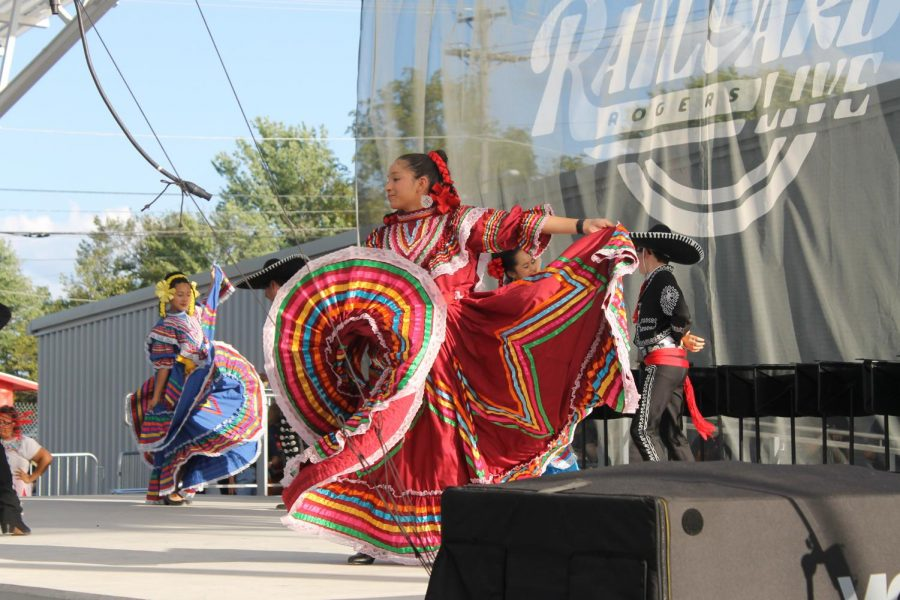 A woman in traditional Mexican dress twirls her pink, red, and yellow skirt during a dance.